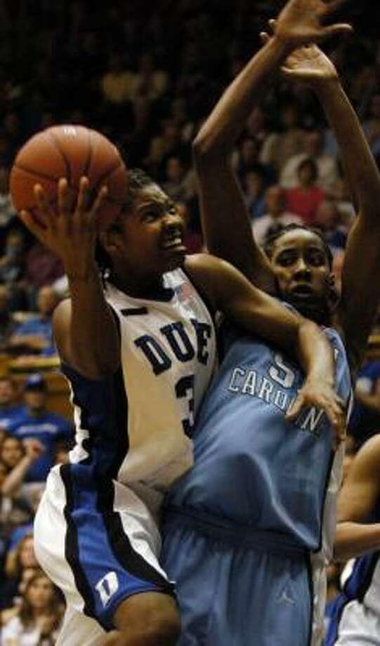 Duke's Keturah Jackson, left, makes a hard drive against Jessica Breland. Photo: SARA D. DAVIS, AP