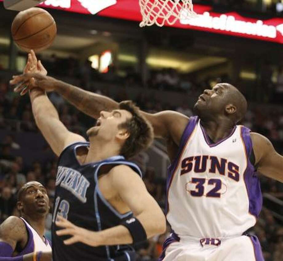 Utah's Mehmet Okur, left, has his shot blocked by Phoenix's Shaquille O'Neal in the first quarter of Friday night's game. Photo: RICK SCUTERI, ASSOCIATED PRESS