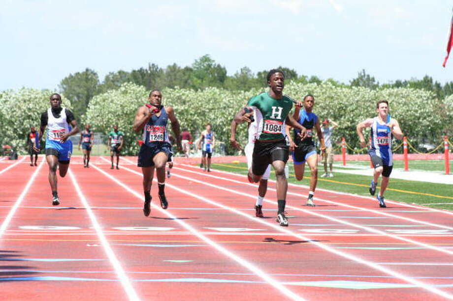 Hightower's Isaiah Sweeney, center, crosses the finish line to cap the Hurricanes' win in the 400-meter relay. Hightower won the race in 40.99 seconds. Photo: Gerald James, For The Chronicle