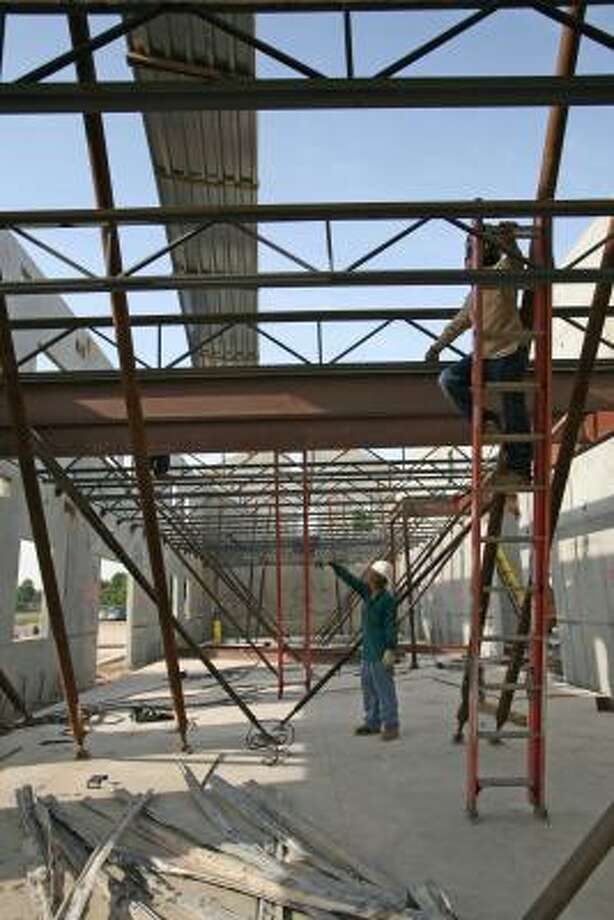 Johnny Sanchez inspects the beams of the new West I-10 Fire Station No. 4, while Pablo Llanes works on the joists up high. Photo: Suzanne Rehak