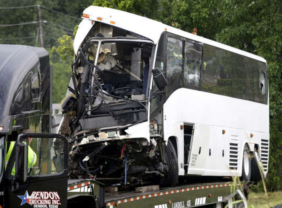The charter bus involved in an early morning accident Friday is carefully negotiated onto a Rendon Trucking Inc. tow truck at the scene of the fatal accident in Sherman. Photo: Stewart F. House, Fort Worth Star-Telegram