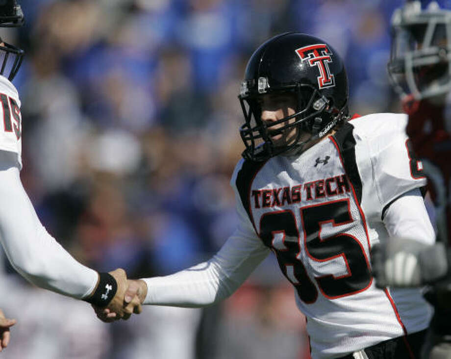 Texas Tech kicker Matt Williams (85) is congratulated by holder Taylor Potts (15) after kicking an extra point in the second half of the Red Raiders' win over Kansas on Saturday. Photo: Orlin Wagner, Associated Press