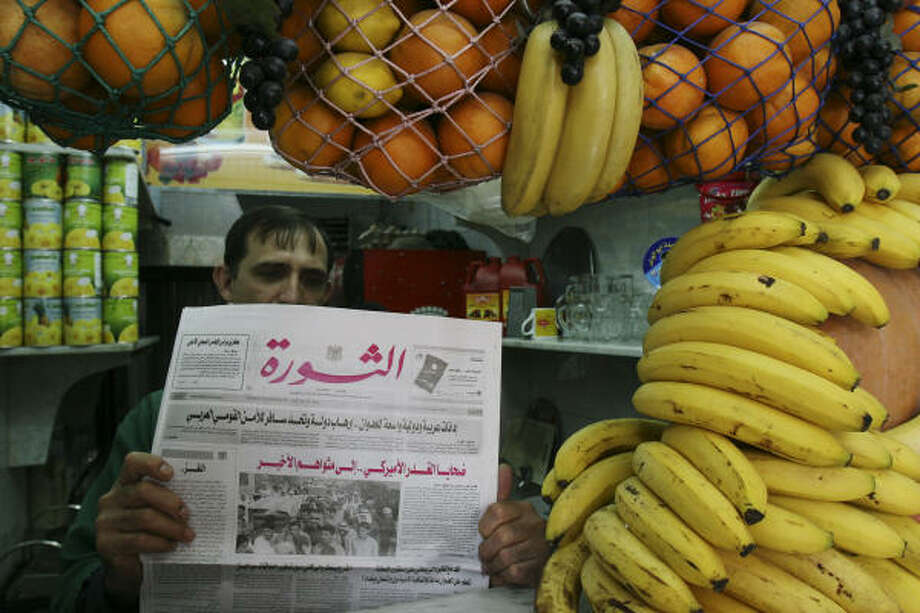 A Syrian man reads a newspaper at his fruit juice store in Damascus, Syria, today. Photo: BASSEM TELLAWI, AP