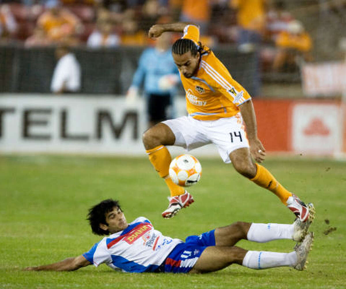 Dynamo midfielder Dwayne DeRosario leaps over a sliding L.A. Firpo defender Edgar Fernando Lequizarron during the Dynamo's CONCACAF Champions League group-stage match against Salvadoran club Luis Angel Firpo on Wednesday at Robertson Stadium.
