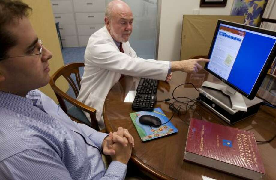 Dr. David Poplack talks with long-term cancer survivor Kevin Alexander about the new Passport for Care program, a new Web-based resource for patients that Poplack developed. Photo: BRETT COOMER, CHRONICLE