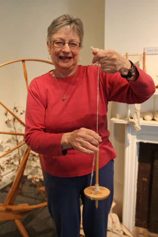 DOCENT SPINS HISTORY: Barbara Neeper of Richmond teaches spinning classes at the Moore Home in Richmond. Here, she demonstrates the drop spindle. Photo: Suzanne Rehak, For The Chronicle