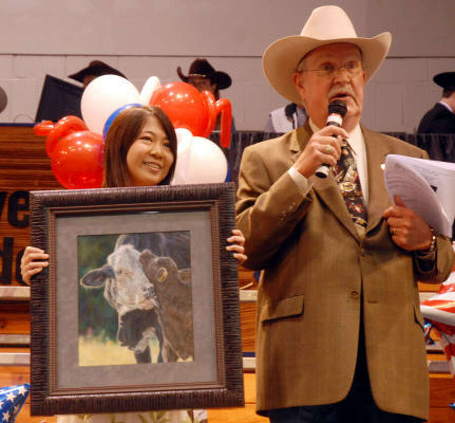 Grand Champion winner Renee Zhan of Katy ISD holds her winning drawing while Bill Bailey talks to the crowd at the School Art Auction on Sunday. Photo: Dave Rossman, For The Chronicle