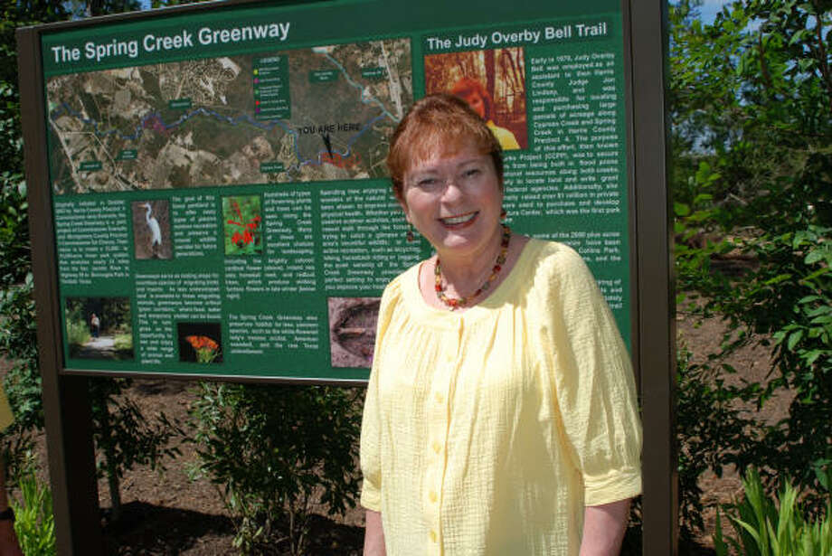 IN HER HONOR: Judy Bell stands in front of the trailhead sign dedicated in her honor at Jesse H. Jones Park and Nature Center.