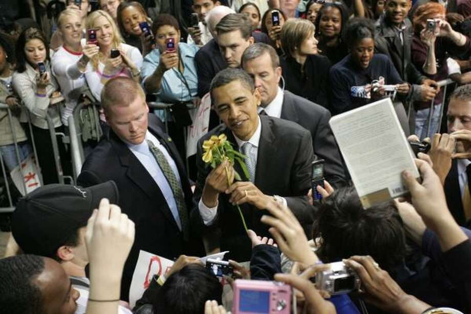 Barack Obama receives a flower from Fatima Tazeen, of Bedford, after speaking at a rally of 16,000 people at Reunion Arena in Dallas. The candidate has a cold, which could hamper him in tonight's debate. At one point, he apologized to the crowd for his hoarse voice. Photo: R. JEENA JACOBS, FORT WORTH STAR-TELEGRAM