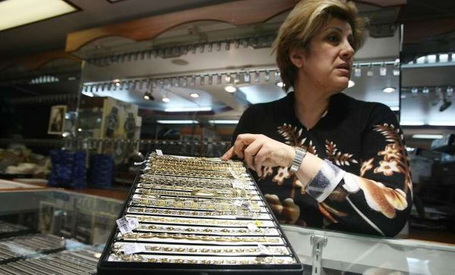 Larisa Aranbayev displays gold bracelets in New York's diamond district on Thursday. Gold remains about $20 away from the psychological mark of $1,000 an ounce. Photo: MARIO TAMA, GETTY IMAGES