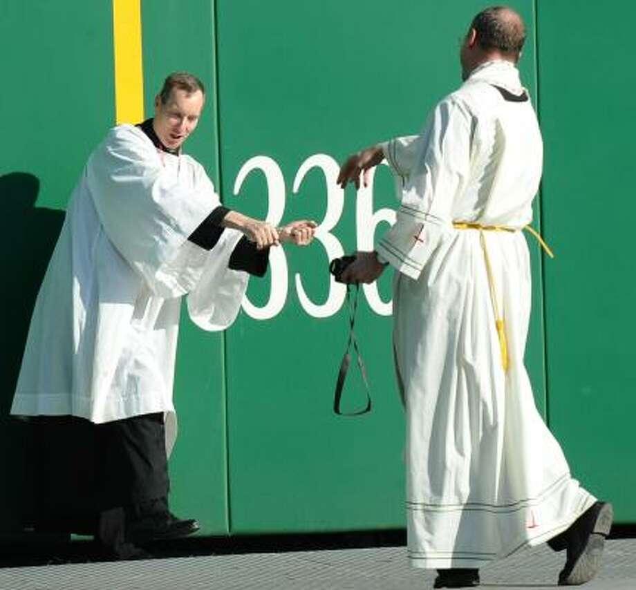 """Priests play """"baseball"""" before Pope Benedict XVI's celebration of Mass on Thursday at Nationals Park in Washington, D.C. Photo: VINCENZO PINTO, AFP/GETTY IMAGES"""