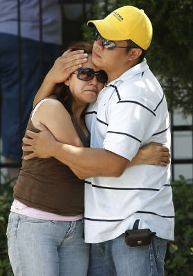 Miguel Cruz comforts his wife Concepción as firefighters put out the fire that destroyed their home at the Towne Lake apartment Homes on Friday. Two minor injuries were reported and two firefighters suffered minor, heat-related exhaustion. Photo: Kevin Fujii, Chronicle