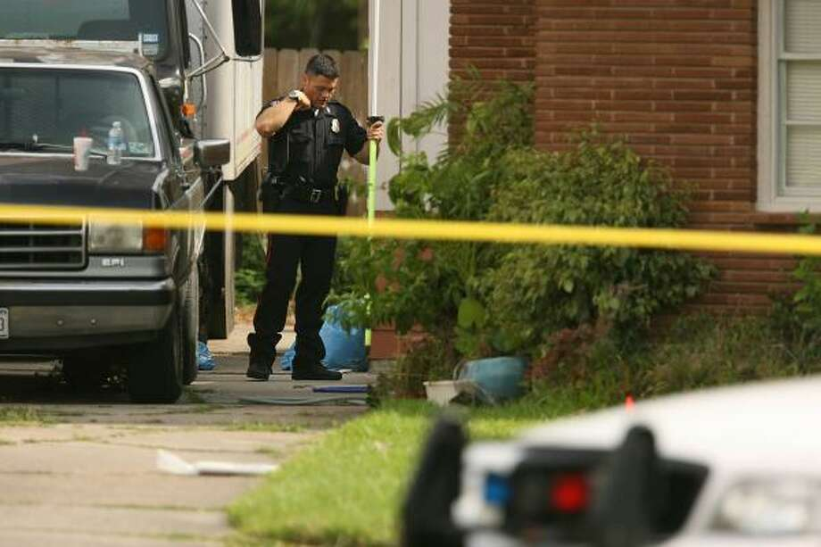 A Pasadena police officer examines where a teen was shot, with three bullet wounds in the right side of his lower back early Friday, after ignoring officers' warnings. For video, go to chron.com/metro. Photo: MAYRA BELTRÁN, CHRONICLE