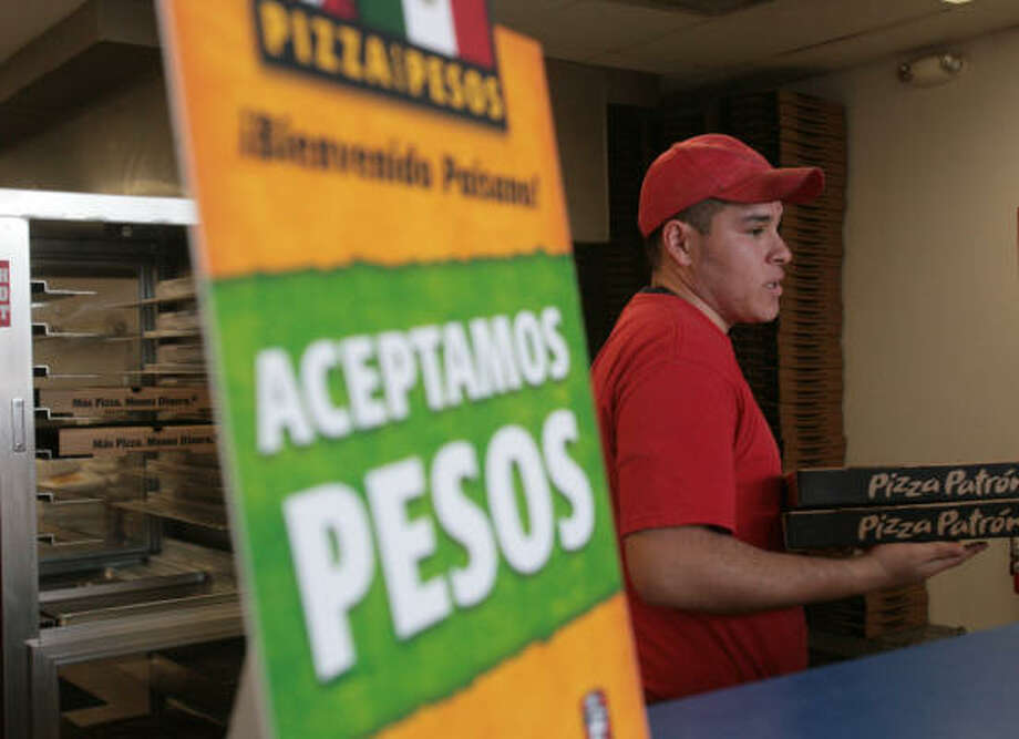 "Jorge Gutierrez carries pizzas at Pizza Patron, near a sign that says in Spanish, ""We accept pesos."" Some customers have criticized the Dallas-based chain for accepting the Mexican currency. Photo: Mayra Beltran, Chronicle"