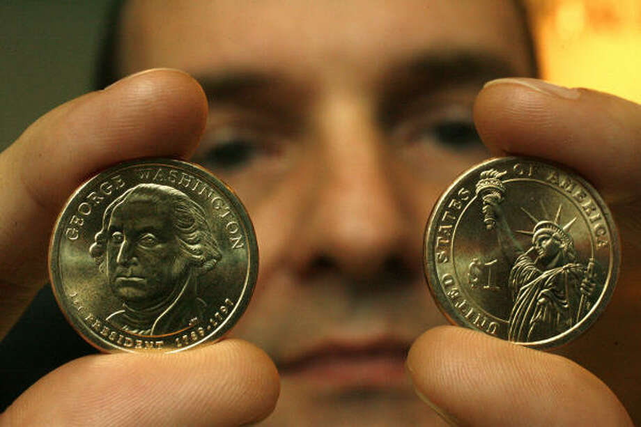 Kenneth Rollo of the Houston branch of the Federal Reserve Bank holds the first in a series of $1 coins. Photo: Billy Smith II, CHRONICLE
