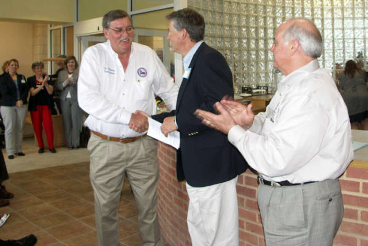 Montgomery County Precinct 4 Commissioner Ed Rinehart, left, receives a congratulatory handshake from Precinct 2 Commissioner Craig Doyle at the March 30 grand opening celebration for the Tullis Library, while Precinct 1 Commissioner Mike Meador looks on.