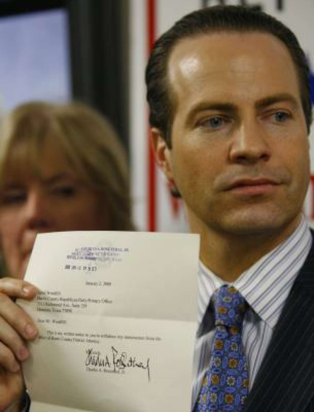 County GOP Chairman Jared Woodfill displays a letter filed by District Attorney Chuck Rosenthal removing his name from the ballot. Woodfill, also a lawyer, said the Texas secretary of state's office and county attorney's office assured him the letter had complied with the law, which does not mention notarization.