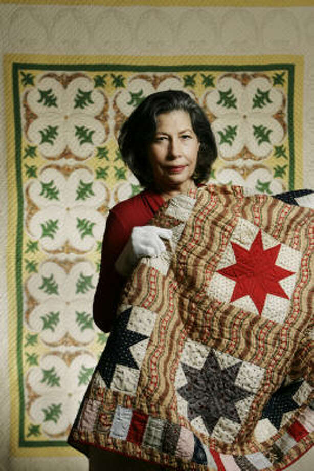 Master Piece Workcurator Mary Evelynn Sorrell holds the 1940 Stars With Wavy Sashing, made by Bertha Stenge. Behind her is Stenge's Tiger Lily, also from 1940. Photo: Eric Kayne, Chronicle