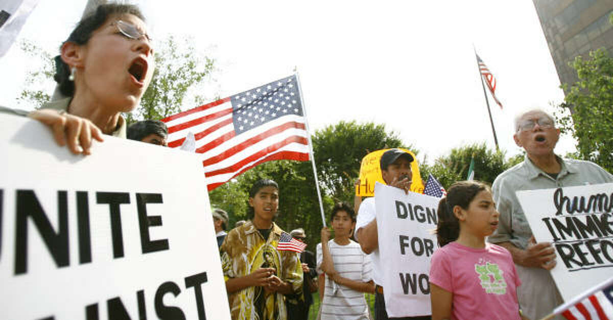 """Rona Smith of La Marque chants during an immigration reform demonstration at the George Thomas """"Mickey"""" Leland federal office building in Houston on Friday."""