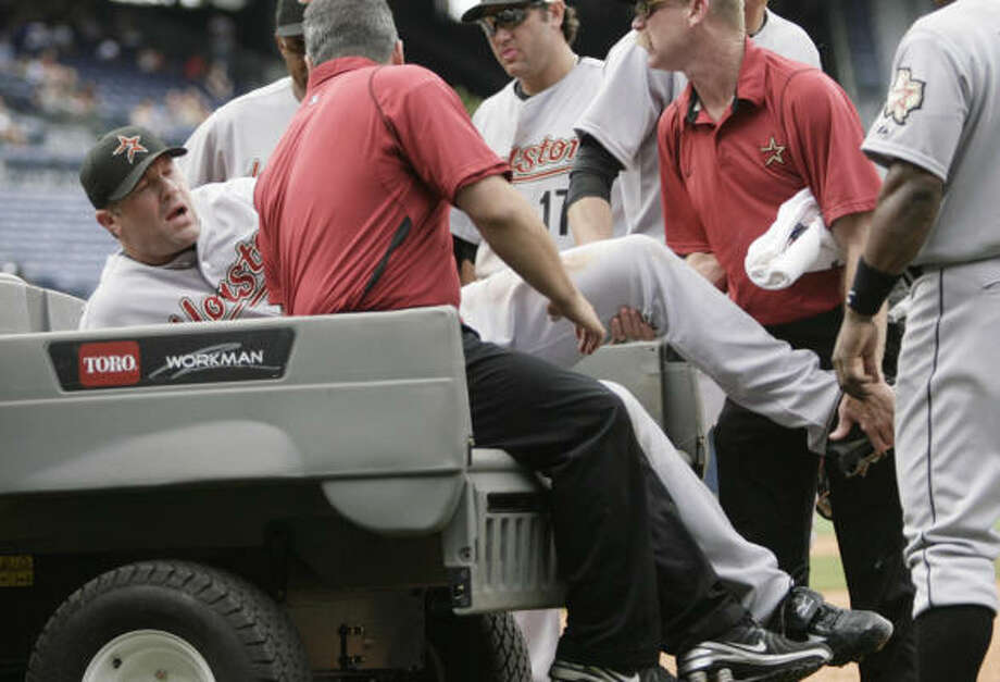 Astros reliever Doug Brocail cringes as he is helped onto a cart after injuring his hamstring on a play at first base in the eighth inning. Photo: John Amis, AP