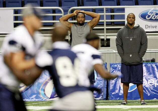 Defensive ends Marcus Spears (left) and Kenyon Coleman watch drills at the morning session of Dallas Cowboys training camp Sunday, July 31, 2011 at the Alamodome. Photo: EDWARD A. ORNELAS, Edward A. Ornelas/eaornelas@express-news.net / © SAN ANTONIO EXPRESS-NEWS (NFS)