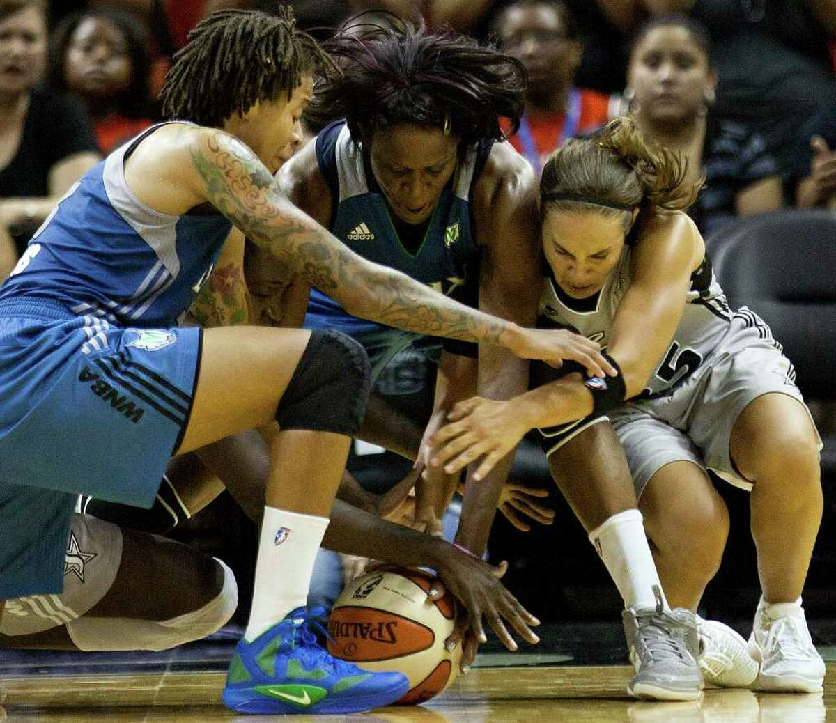 Silver Stars guard Becky Hammon fights Minnesota Lynx players Taj McWilliams-Franklin and Seimone Augustus for a loose ball on Sunday, July 31, 2011, at the AT&T Center. Hammon had 15 points in the Stars' 70-69 loss to the Lynx.