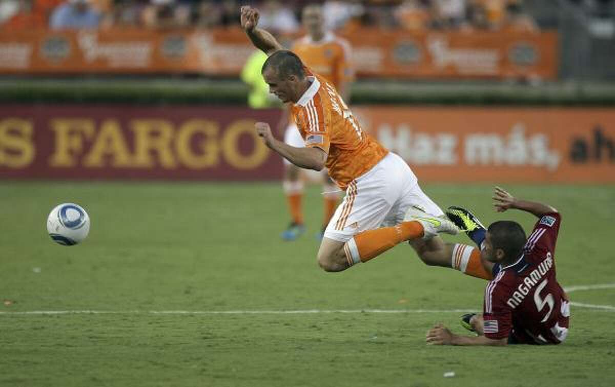 Dynamo forward Cam Weaver, left, is tripped up by Chivas USA's Paulo Nagamura as he goes for the ball.