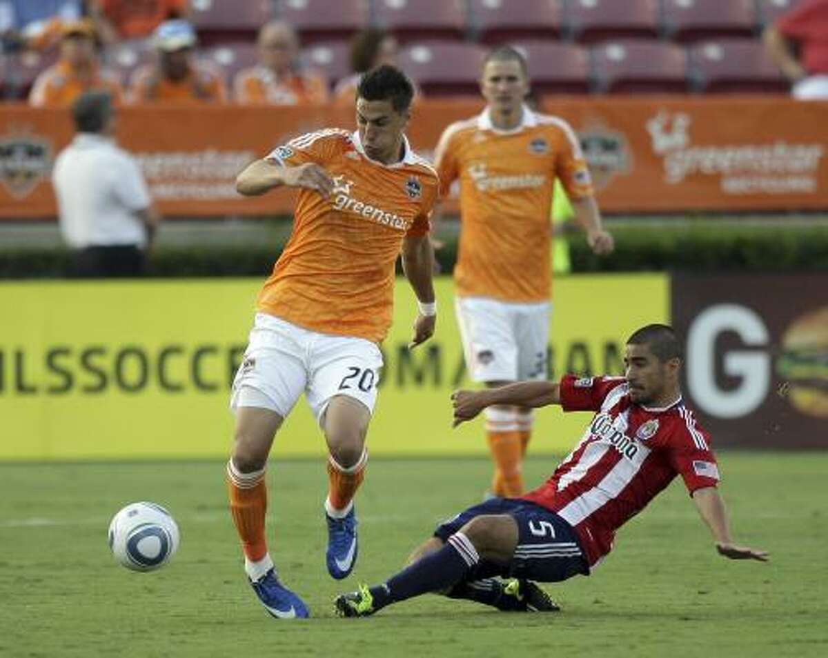 June 11: Dynamo 2, Chivas USA 1 Dynamo foward Geoff Cameron, left, avoids a sliding tackle from Chivas USA's Paulo Nagamura during Saturday's match at Robertson Stadium. Weaver scored in the 29th minute to held propel the Dynamo to their first win since April 29.