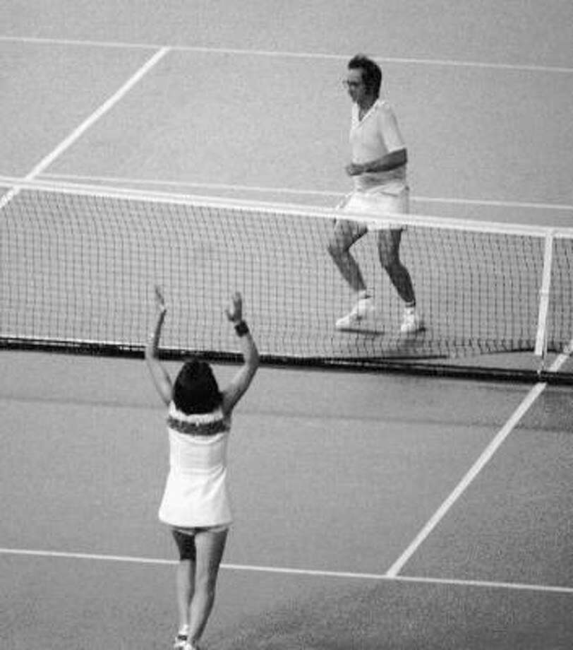 "Billie Jean King raises her arms after defeating Bobby Riggs, rear, getting ready to jump over the net, in the ""Battle of the Sexes"" game at the Houston Astrodome in 1973 Photo: AP"