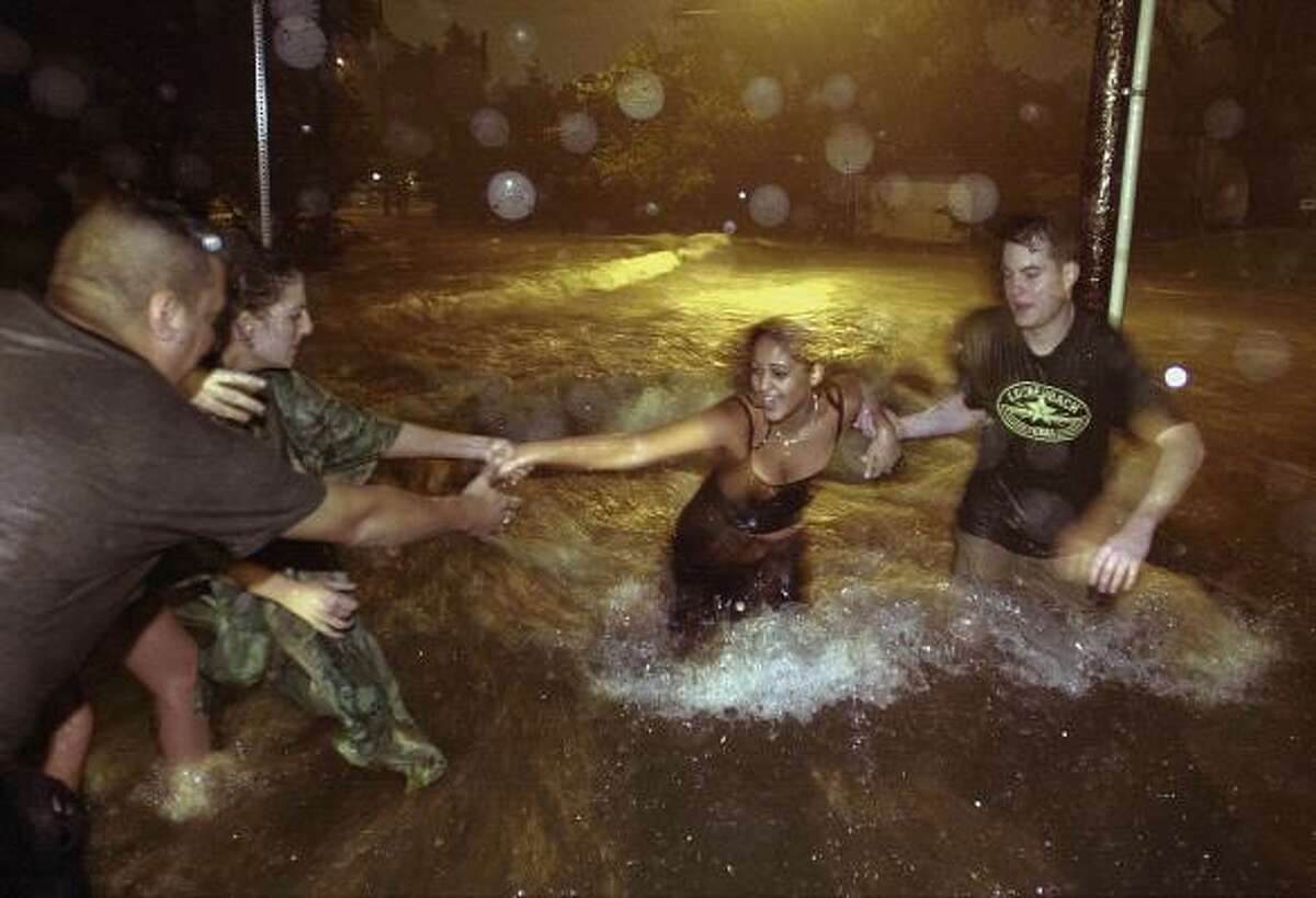 Sean Torres, left, Julia Demeritt and Ryan Johnson, right, assist Diana Delarosa in the rushing floodwaters on Michaux in Woodland Heights.