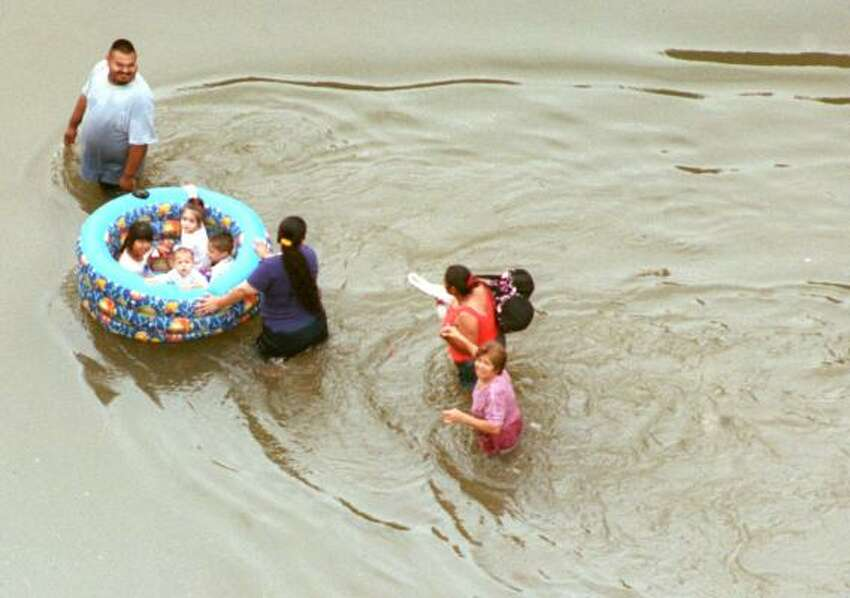 PHOTOS: Devastation and chaos from Tropical Storm Allison (June 2001) A family uses a wading pool to float toddlers out of a neighborhood near I-59.