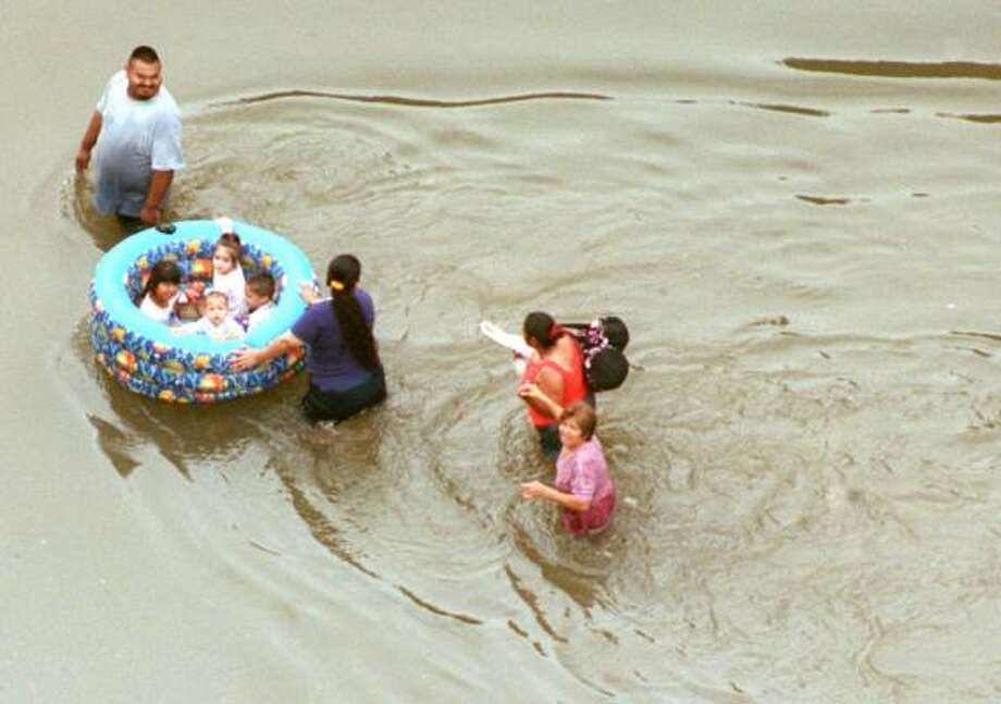 PHOTOS: Devastation and chaos from Tropical Storm Allison (June 2001)A family uses a wading pool to float toddlers out of a neighborhood near I-59. Photo: Ben DeSoto, Houston Chronicle