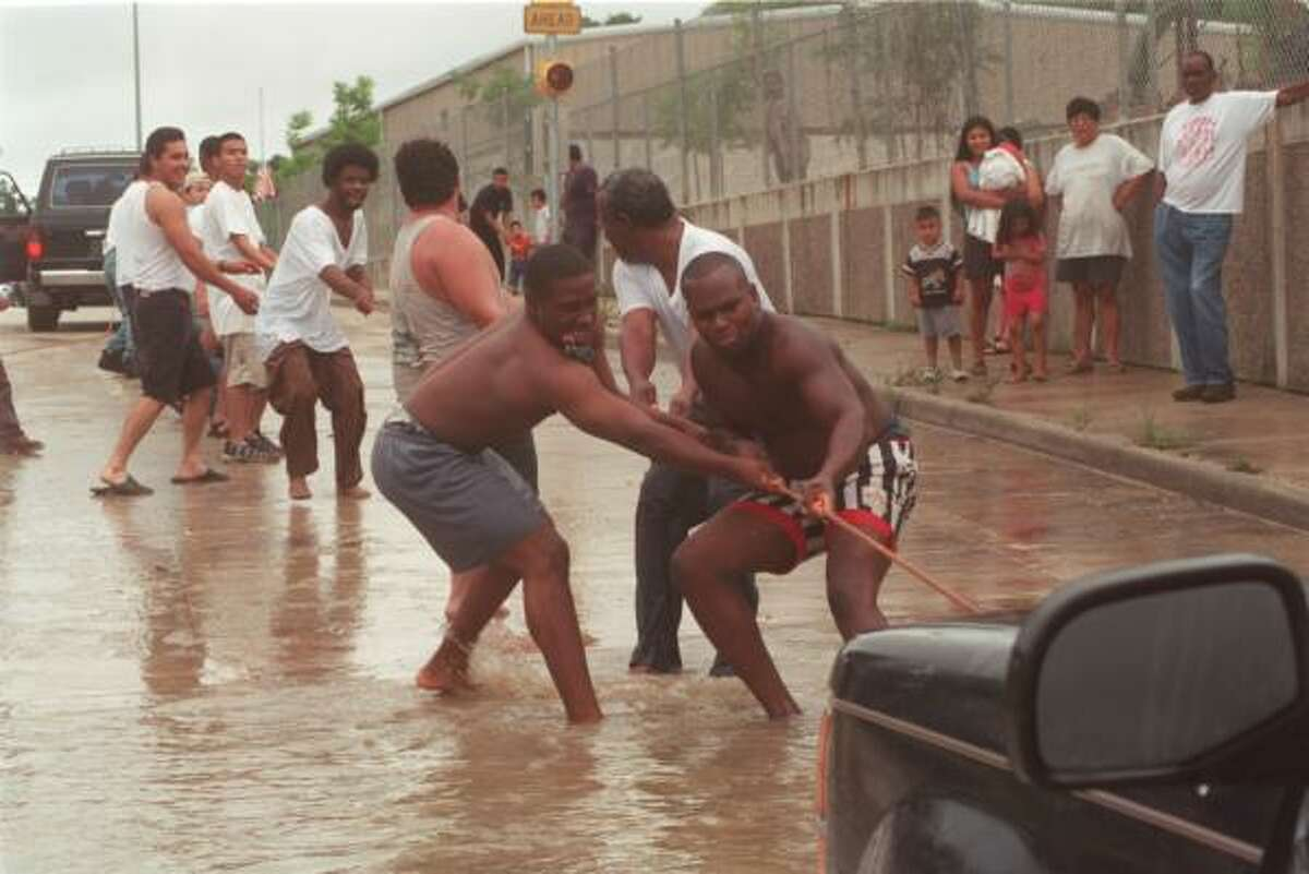 Men tug a truck from the water at Hardy and Crosstimbers after water rose over the tops of cars and trucks following unrelenting rain from Tropical Storm Allison.
