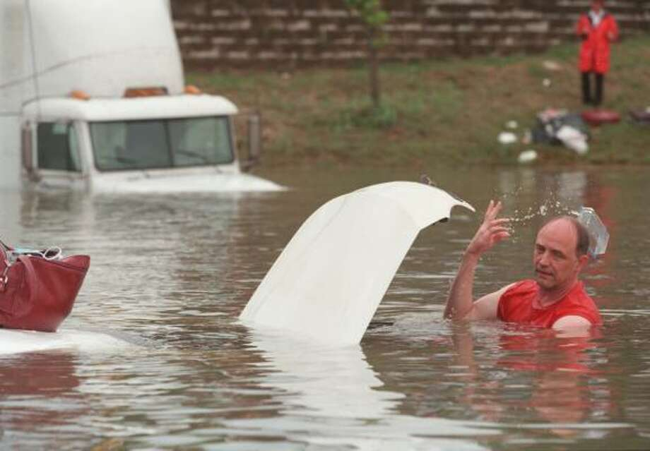 Shoulder-deep in the murky floodwaters that covered Interstate 10 near Shepherd, an unidentified man tosses a worthless article from the trunk of a partially submerged car on the Katy Freeway on June 9, 2001. Heavy rains pounded the city for the five days, causing devastating flooding. Photo: Andrew Innerarity, Houston Chronicle