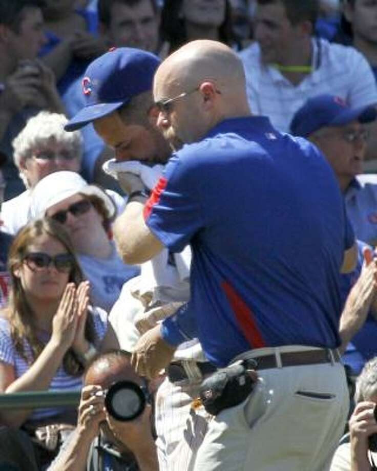 Chicago Cubs third baseman Aramis Ramirez, left, is taken into the dugout by trainer after Ramirez was hit in the mouth by a ball hit by the Astros' Chris Johnson during the seventh inning. Photo: Charles Rex Arbogast, Associated Press