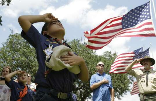 John Baez, 8, of Tomball with Cub Scout Pack 469 salutes as a U.S. flag is raised at the Houston National Cemetery,10410 Veterans Memorial Drive, in Houston. The scouts took part in the raising of 300 U.S. flags measuring 5 foot by 10 foot along the cemetery roadways as part of the Avenue of Flags. Scout units both boys and girls took part in this preparation for the Memorial Day Ceremony, to be held at the national cemetery on Monday, May 30, at 9:30 a.m. Photo: Melissa Phillip, Houston Chronicle