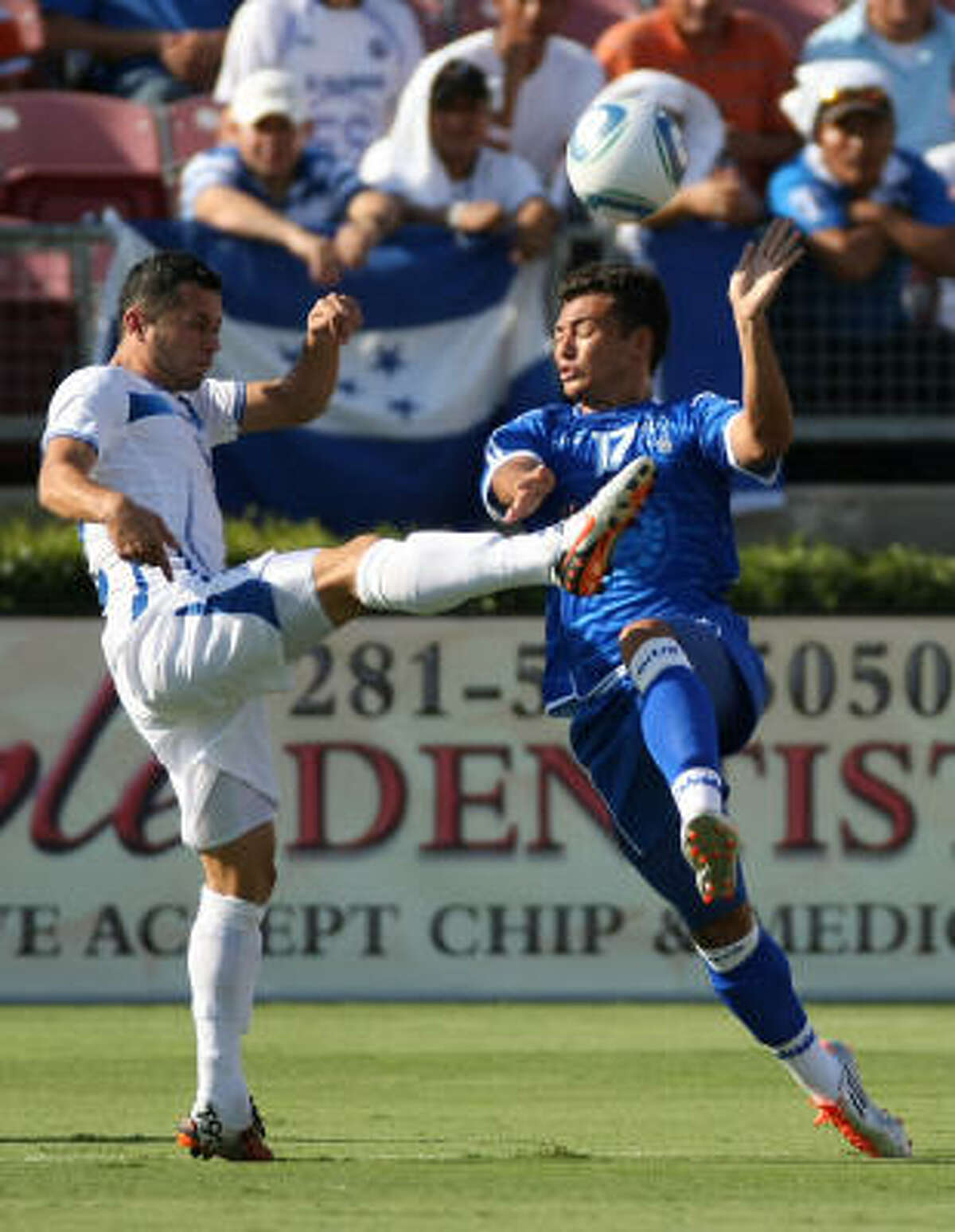 El Salvador's Mark Lester Blanco, right, tries to avoid getting kicked in the face by Honduras' Alfredo Antonio Mejia in the first half.