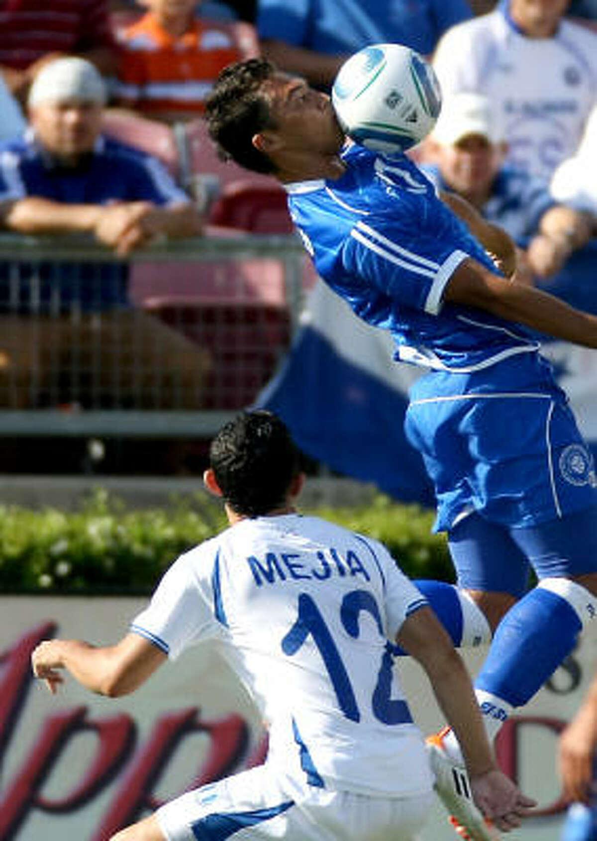 El Salvador's Mark Lester Blanco, top, controls the ball as Honduras' Alfredo Antonio Mejia looks on in the second half.