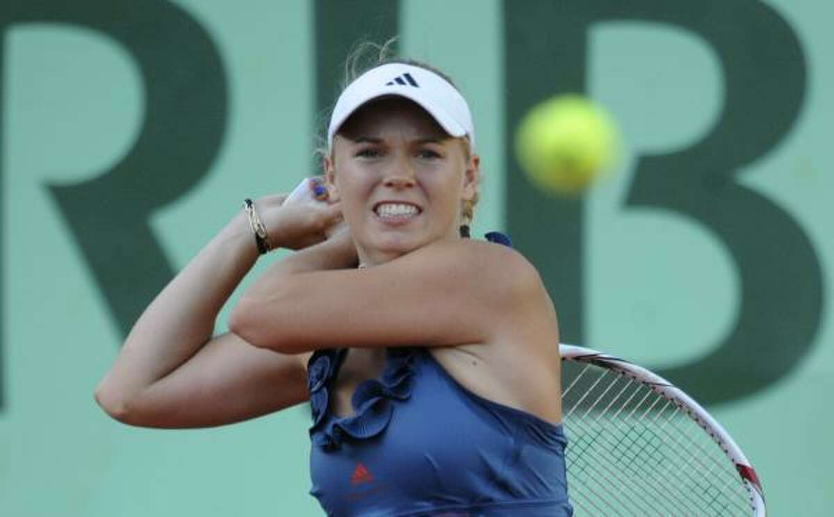 Denmark's Caroline Wozniacki returns the ball to Japan's Kimiko Date-Krumm during their first round match.