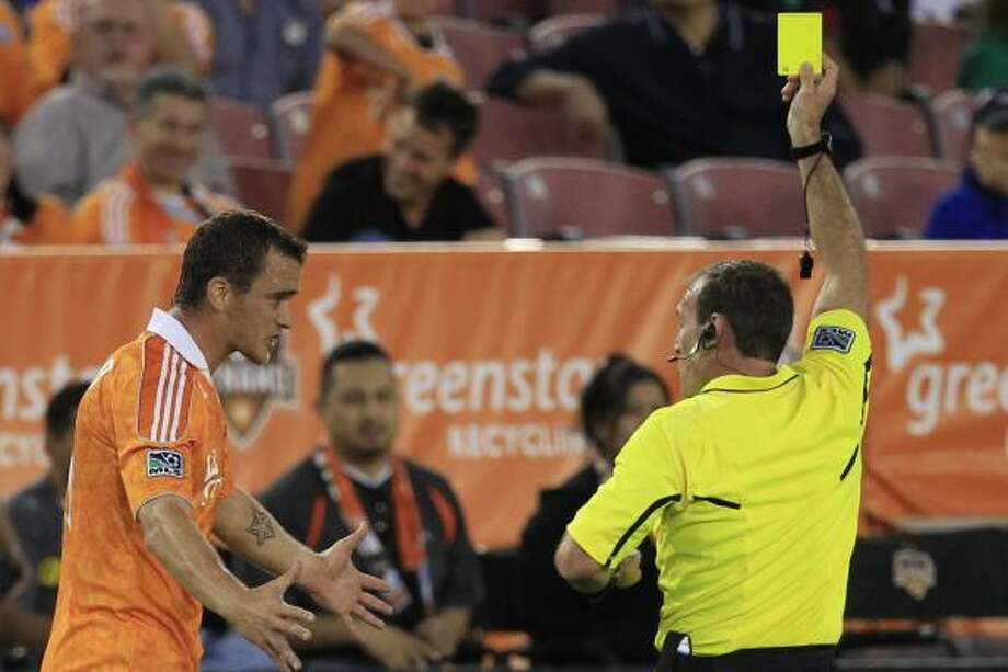 Dynamo forward Cam Weaver (15) gets a yellow card during. Photo: Michael Paulsen, Chronicle