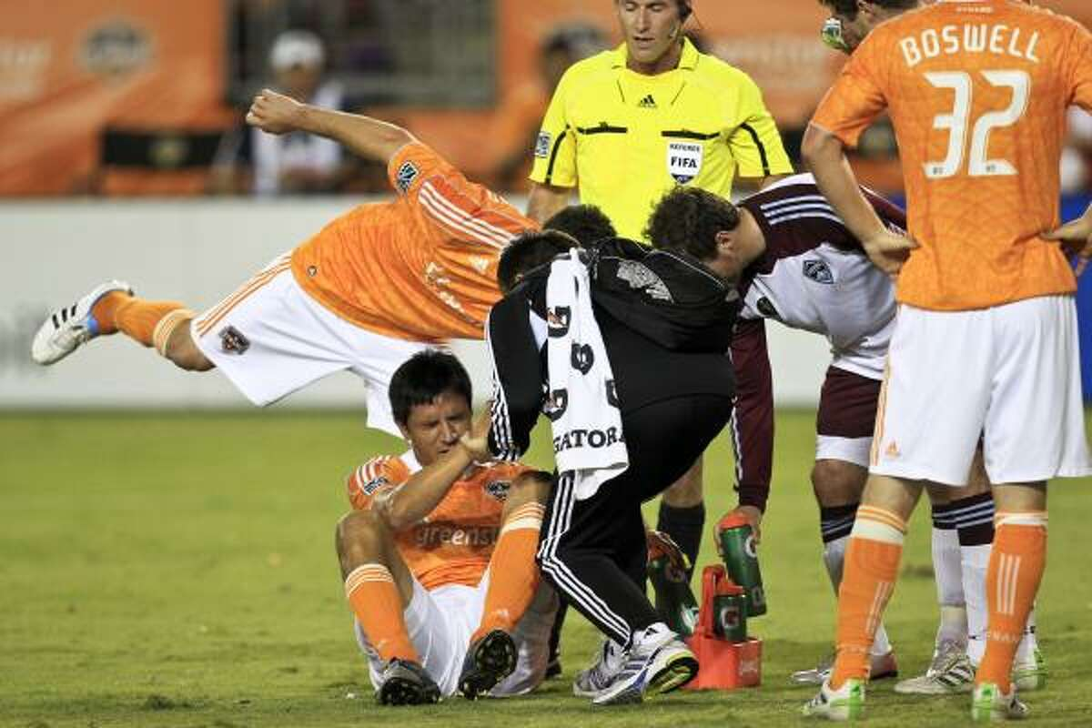 Dynamo forward Brian Ching (25) gets helped off the field after going down hard.