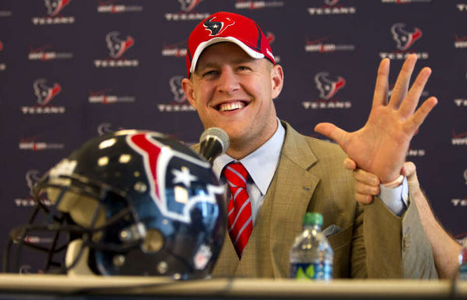 J.J. Watt smiles as his hands is held up by defensive coordinator Wade Phillips. Photo: Brett Coomer, AP