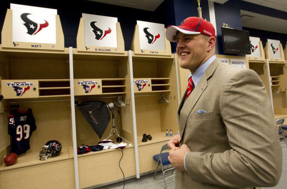 J.J. Watt smiles as he gets ready to have a portrait taken at his locker. Photo: Brett Coomer, Chronicle