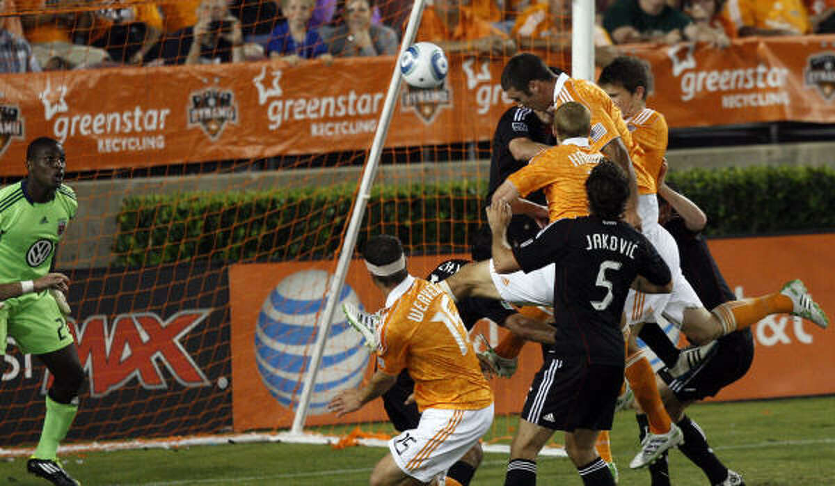 Dynamo forward Will Bruin, center top, scores his third goal of the evening on a header past D.C. United goalkeeper Bill Hamid.