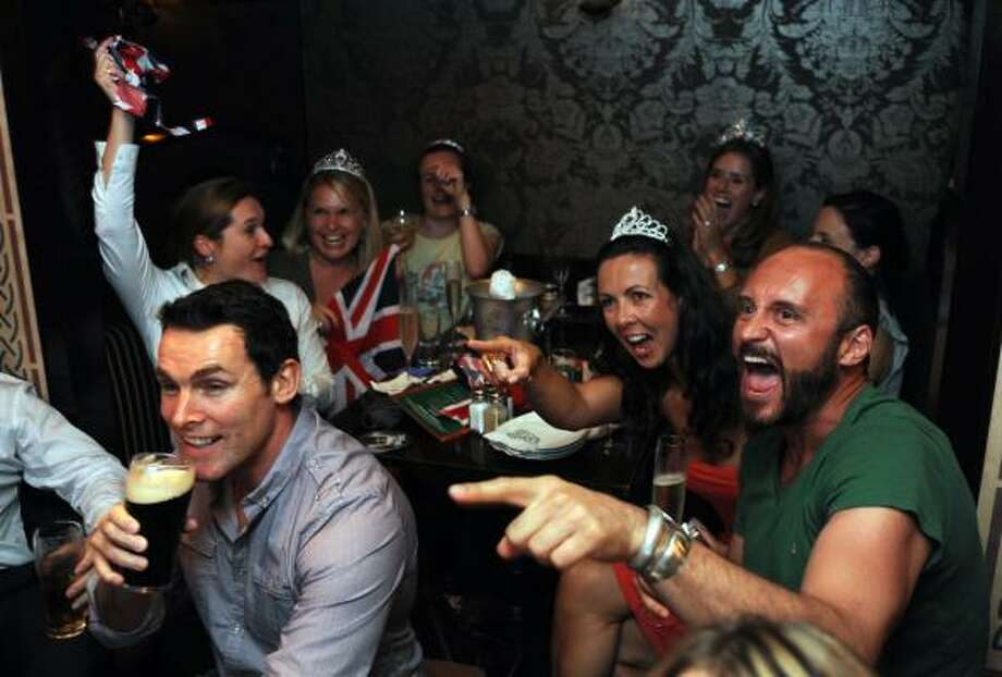 People celebrate the marriage of Prince William and Kate Middleton in a bar in Hong Kong on April 29, 2011.  Clutching Union Jack flags, they had come from all over the world, rising before dawn or camping overnight for the royal wedding, and they were finally rewarded as Prince William and Kate Middleton were declared husband and wife at Westminster Abbey in London.  AFP PHOTO/MIKE CLARKE Photo: MIKE CLARKE, AFP/Getty Images