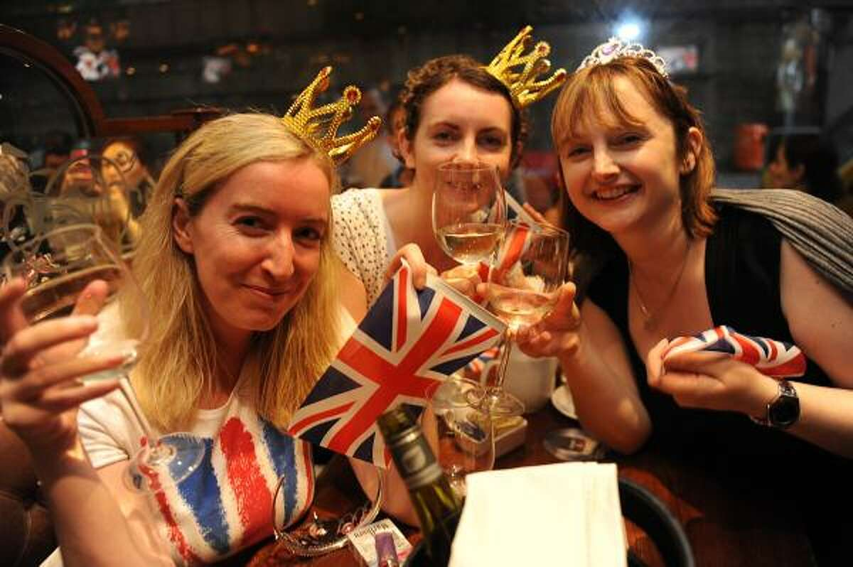 People celebrate the marriage of Prince William and Kate Middleton in a bar in Hong Kong on April 29, 2011. Clutching Union Jack flags, they had come from all over the world, rising before dawn or camping overnight for the royal wedding, and they were finally rewarded as Prince William and Kate Middleton were declared husband and wife at Westminster Abbey in London. AFP PHOTO/MIKE CLARKE