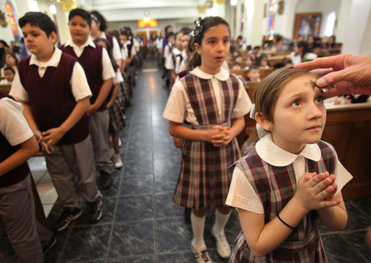 Andrea Castillo, a third grader, and other students of the Our Lady of Guadalupe Catholic School, receive ashes during mass on Ash Wednesday at Our Lady of Guadalupe Church on Wednesday, March 9, 2011, in Houston.