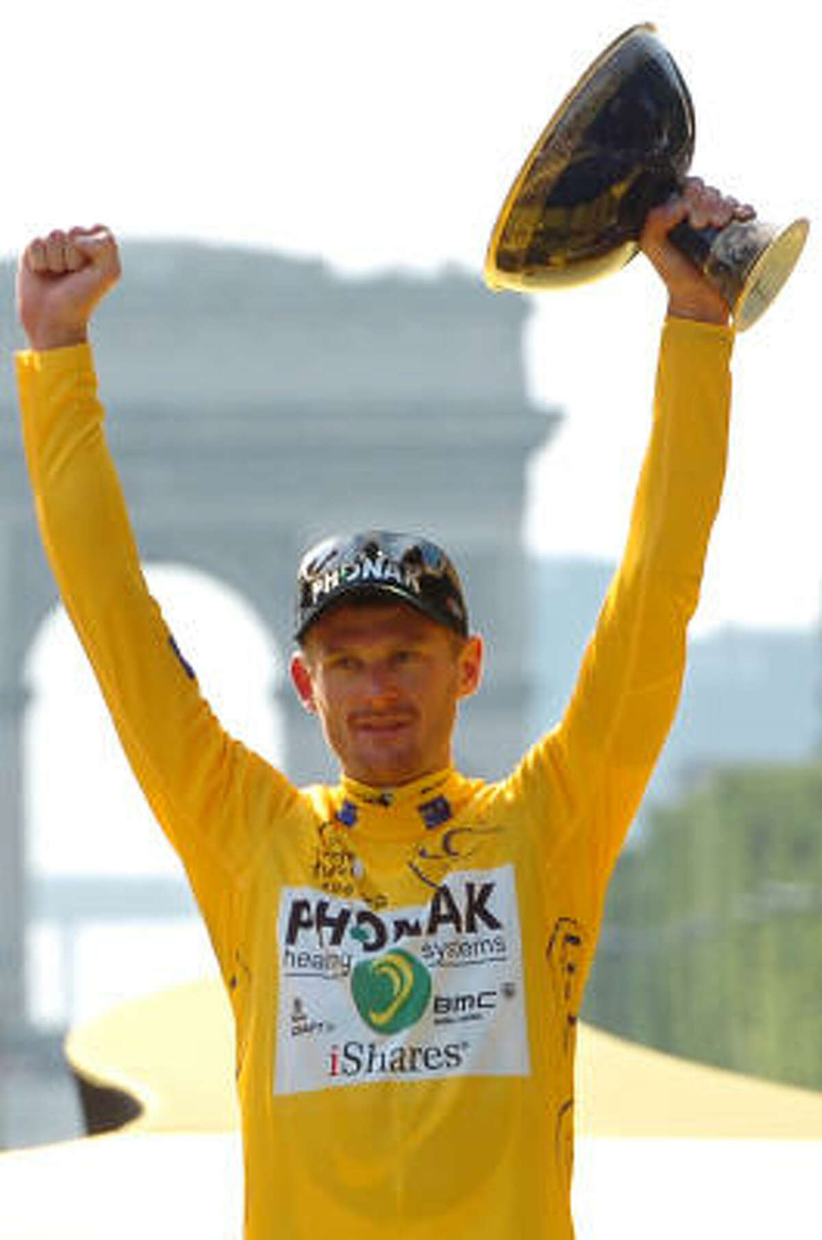 FILE - 2006 Tour de France winner Floyd Landis of the US, holds up his trophy after the final stage of the 93rd Tour de France cycling race between Antony, south of Paris, and Paris, in this July 23, 2006 file photo. France's anti-doping chief said on Monday Feb. 15, 2010 that a French judge has issued a national arrest warrant for U.S. cyclist Floyd Landis in connection with a case of data hacking at a doping laboratory.
