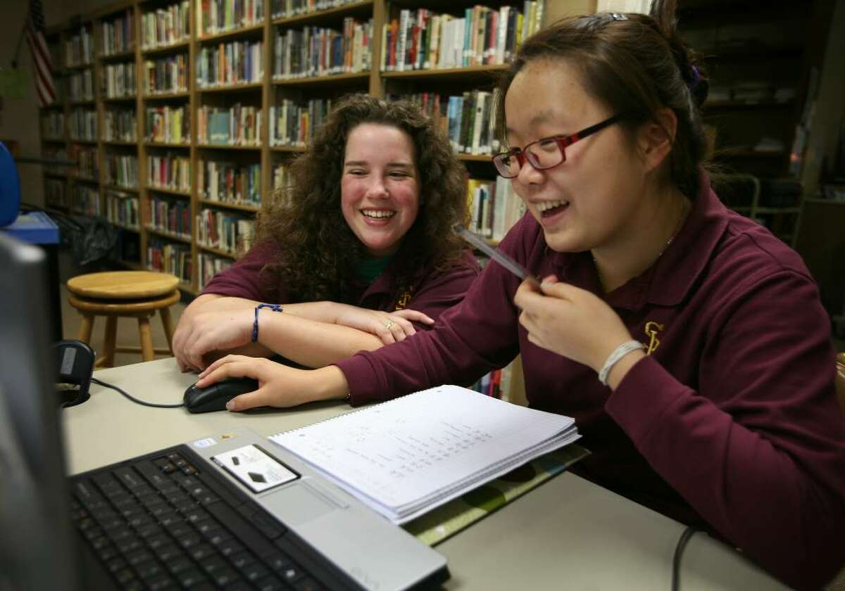 St. Joseph High School seniors Megan Glynn, left, 16 of Trumbull, and Yoona Kim, 17 of Oxford, take classes over the internet through a program called Virtual High School. Glynn takes Advanced Placement French, while Kim, a native of Korea, studies Mandarin Chinese.