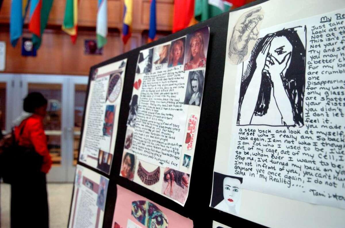 University of Bridgeport student Iris Grattan admires the art work done by domestic violence survivors on display Thursday at the school's John J. Cox Student Center.